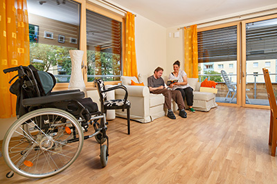 Wohnzimmer einer Wohngemeinschaft von Pro Mobil, ein Rollstuhl im Vordergrund