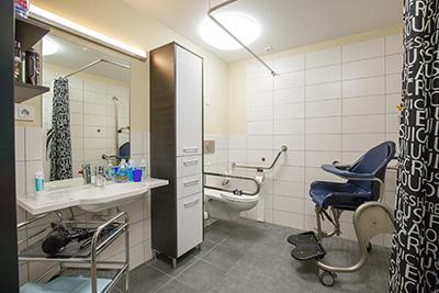 Badezimmer einer Wohngemeinschaft von Pro Mobil, ein Rollstuhl im Vordergrund