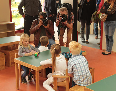Vier Kinder sitzen in der Kita Kleine Robbeninsel an einem Tisch und werden von Pressefotografen fotografiert