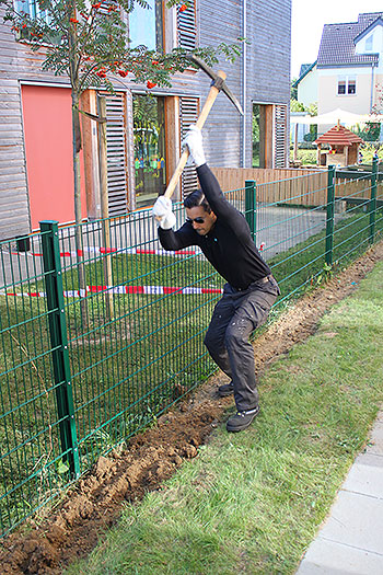 Mann mit einer Axt schlägt einen Graben in ein Rasenstück