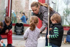 Zu sehen sind Eltern und Kinder beim bearbeiten des Beetes